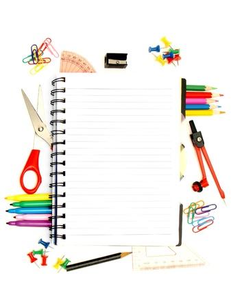 utiles escolares: Port�til en blanco rodeado por un borde de escuela diversos suministros Foto de archivo