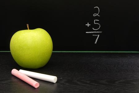 Teachers apple and chalk on desk with blackboard background