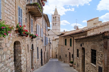 Narrow medieval street in the hill town of Assisi with the church of St Clare in the background