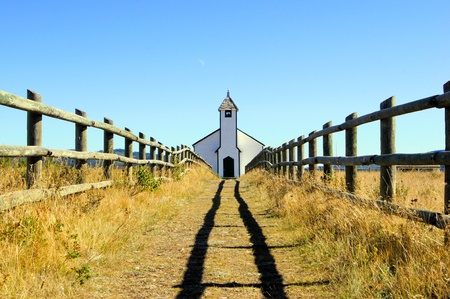 blue church: Symmetric view of a small wooden church in the prairies during autumn