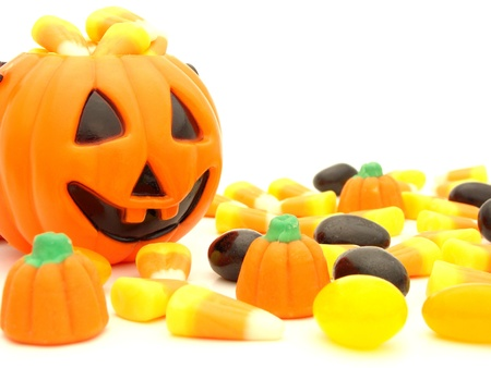 Halloween pumpkin behind a pile of scattered assorted candies against a white background photo