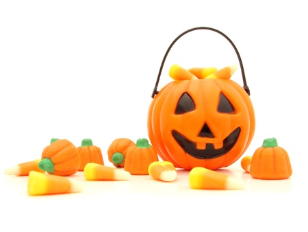 Halloween pumpkin and a pile of scattered assorted candies against a white background Stock Photo
