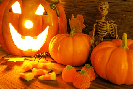 Halloween night scene closeup with glowing jack-o-lantern, pumpkins, candy and skeleton photo