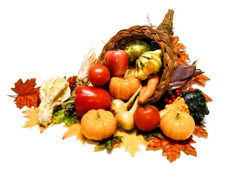 Harvest or Thanksgiving cornucopia filled with wide selection of vegetable over a white background photo