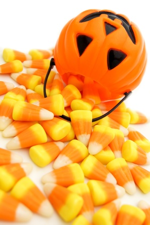 Pumpkin candy holder with spilling Halloween candy corn on a white background photo