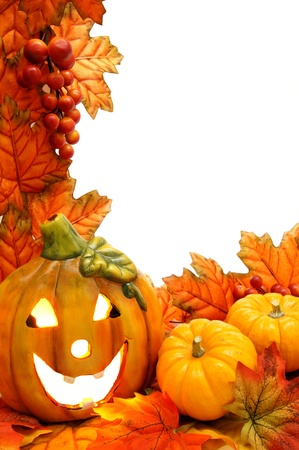 Vertical border with jack-o-lantern and fall leaves with white background photo