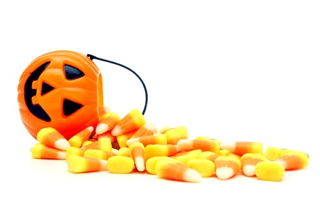 Pumpkin candy holder with spilling Halloween candy corn over white Stock Photo - 10844242