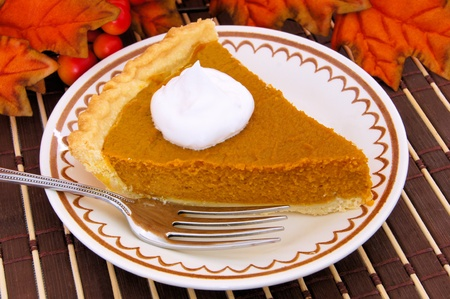 Slice of pumpkin pie on a plate with red autumn leaves in the background photo
