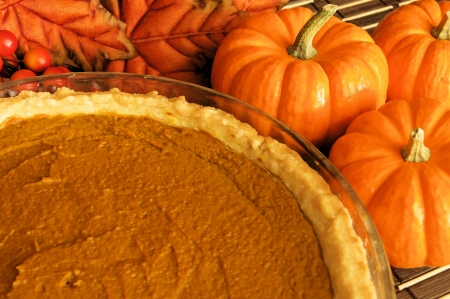 Fresh pumpkin pie in a pie plate with pumpkins and autumn leaves in the background