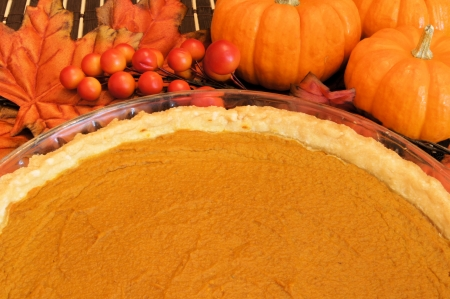 Fresh pumpkin pie in a pie plate with pumpkins and autumn leaves in the background photo