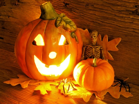 candle holder: Halloween night scene with lit jack o lantern, pumpkin, skeleton and spiders Stock Photo