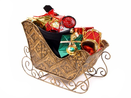 Santa Claus Sleigh and bag filled with Colorful Gifts and Toys over white  photo