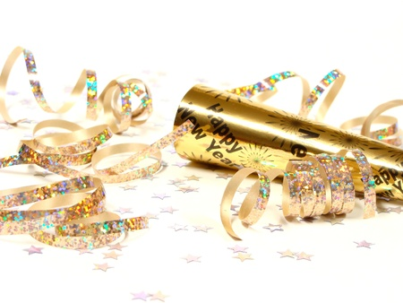 New Years Eve Noisemaker and scattered Party Confetti over white