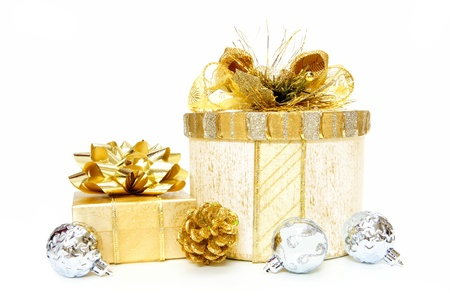 Gold Christmas gift boxes with bows and ribbon and bauble decorations over white photo