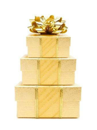 three gift boxes: Pila de cajas de regalo de Navidad de oro con el arco y la cinta sobre un fondo blanco