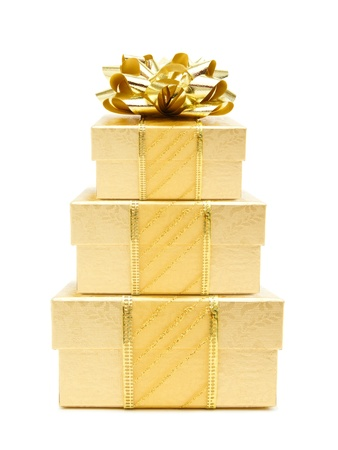 three presents: Stack of gold Christmas gift boxes with bow and ribbon over a white background