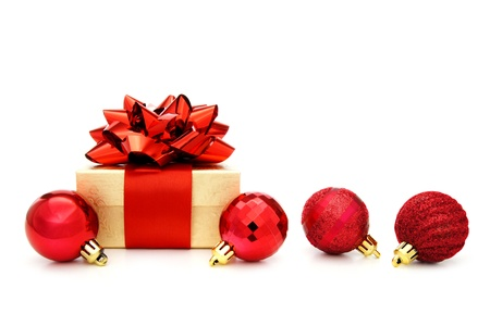 Gold Christmas gift box with red bow and red bauble decorations on a white background