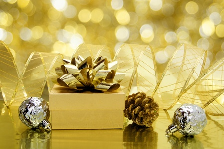 Christmas gold themed still life with gift box, baubles, ribbon and abstract light background photo
