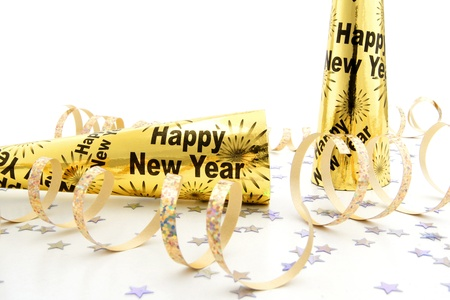 New Years Eve party noisemakers with confetti and streamers over a white background