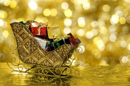 Christmas sleigh filled with gifts with golden background photo
