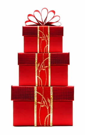 christmas gift: Stacked red Christmas gift boxes with ribbon and bow isolated on a white background Stock Photo