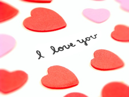 Hand written I Love You message with heart-shaped confetti photo