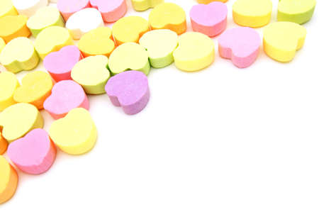 scattered in heart shaped: Valentines Day candy background or corner border over white