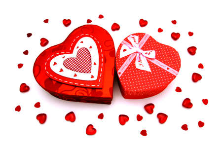 Two Valentines Day heart-shaped gift boxes with gems and confetti over white photo