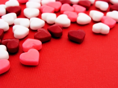 Colorful heart-shaped candy on red textured paper background