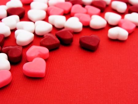 Kleurrijke hartvormige snoepjes op rode getextureerd papier achtergrond
