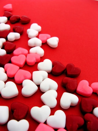 textured paper background: Colorful heart-shaped candy on red textured paper background