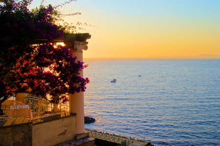 positano: View from Sorrento, Italy at dusk from a flower draped terrace Stock Photo