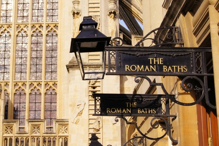 Iron signs for the Roman Baths of Bath England in front of the Abbey photo