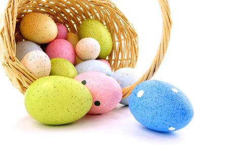 pascuas navide�as: Derramar la cesta de Pascua de los huevos de colores sobre un fondo blanco