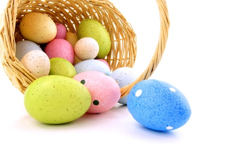 Spilling Easter basket of colorful eggs over a white background