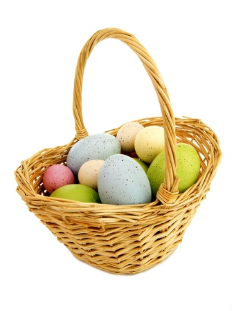 basket: Easter basket filled with colorful eggs isolated on white
