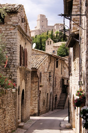 narrow: Medieval street in the Italian hill town of Assisi with castle in the background Stock Photo