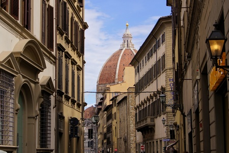 Classic old street in the center of Florence, Italy with duomo dome in background photo
