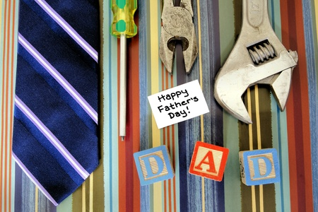 Collection of tools with tie and Fathers Day tag over a masculine patterned background
