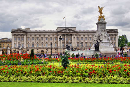 Buckingham Palace behind vibrant red flower garden