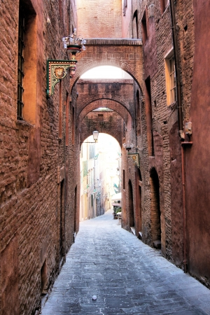Narrow medieval arched street  - Siena, Italy photo