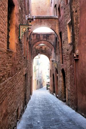 arcuate: Stretta strada medievale ad arco - Siena, Italia Archivio Fotografico
