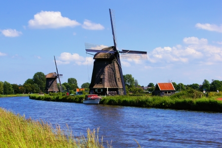 View of traditional Dutch windmills along a canal near Alkmaar, The Netherlands Stock Photo - 14332534