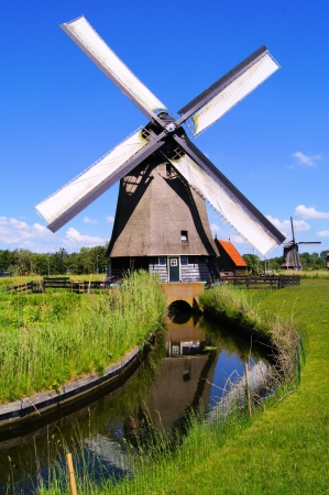 Traditional Dutch windmill along a canal near Alkmaar, The Netherlands during summer Stock Photo - 14332549