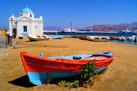 greece shoreline: Old boat and traditional blue dome church on the shore of Mykonos island, Greece