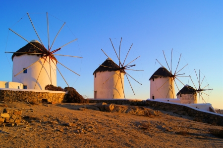 Famous row of traditional Greek windmills at sunset, Mykonos, Greece photo