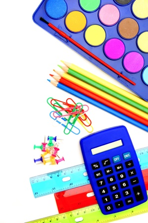 Colorful school supplies arranged as a border over white photo