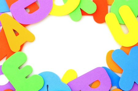 Colorful toy spelling letters forming a frame over white