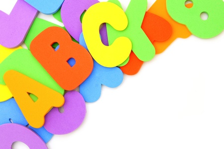 Colorful toy spelling letters forming a corner border over white photo