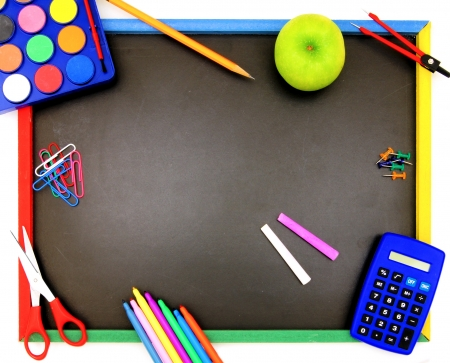 Blank blackboard with various colorful school supplies surrounding it photo